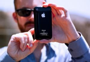 man holding iphone using iphone logo back apple