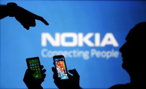 Men are silhouetted against a video screen with an Nokia logo as he poses with an Nokia Lumia 820 and Samsung S4 smartphones in this photo illustration taken in the central Bosnian town of Zenica