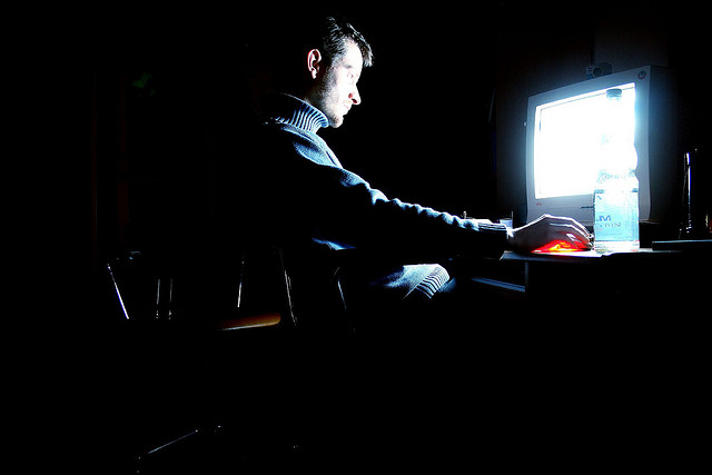 man using computer in dark room screen glow privacy security