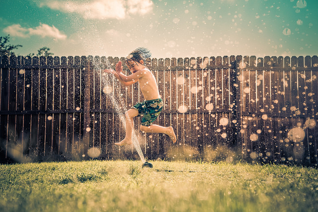 boy running through sprinker backyard hydration system
