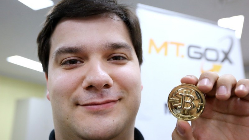 Mark Karpeles, chief executive officer of Tibanne Co., poses for a photograph with a bitcoin in the office operating the Mt.Gox K.K. bitcoin exchange in Tokyo, Japan, on Thursday, April 25, 2013. Bitcoin digital currency, which carries the unofficial ticker symbol of BTC, was unveiled in 2009 by an unidentified programmer, or group of programmers, under the name of Satoshi Nakamoto. Supply is capped at 21 million Bitcoins and managed by a software algorithm embedded into the digital currency?s design, rather than a monetary authority such as a central bank. Photographer: Tomohiro Ohsumi/Bloomberg via Getty Images